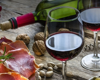 assortment of cheese, nuts and grapes with two glasses of red wine